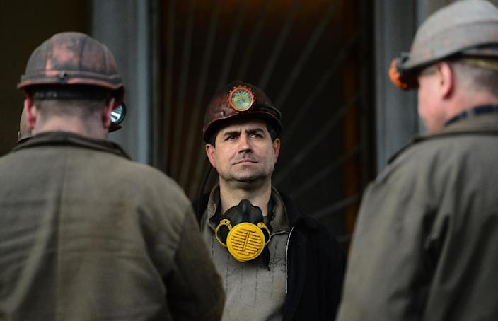 Miners active in the rescue operation take a break before unloading the remains of their dead colleagues at Donetsk's hospital on March 5, 2015 (AFP Photo/John MacDougall)