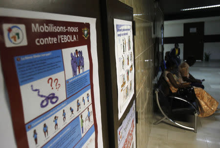 People sit near a poster with a government message against Ebola, at the health minister's office in Abidjan