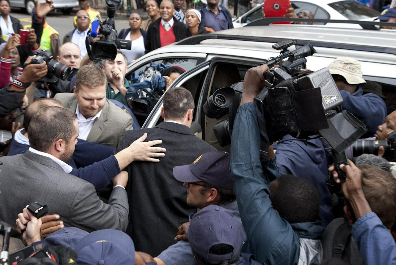 Oscar Pistorius, center, escorted into the car out by his private security and police officers at the high court after the second day of his trial in Pretoria, South Africa, Tuesday, March 4, 2014. Oscar Pistorius is charged with murder for the shooting death of his girlfriend, Reeva Steenkamp, on Valentines Day in 2013. (AP Photo/Themba Hadebe)