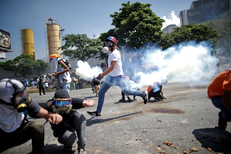 "Opposition demonstrators take cover from tear gas on a street near the Generalisimo Francisco de Miranda Airbase ""La Carlota"" in Caracas, Venezuela April 30, 2019. (Photo: Ueslei Marcelino/Reuters)"