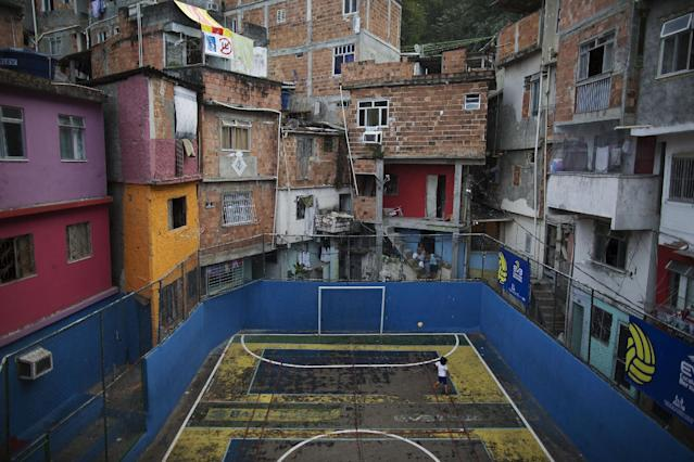 In this April 27, 2014 photo, a boy plays alone as he practices scoring in a small court in the Tavares Bastos shantytown in Rio de Janeiro, Brazil. The high costs of preparing for the 2013 Confederations Cup and upcoming World Cup, blamed in part by the late rush to get projects done, ignited a wave of public criticism from a population already tired of poor public services and widespread corruption, yet in Brazil, soccer is a unifying force. (AP Photo/Leo Correa)