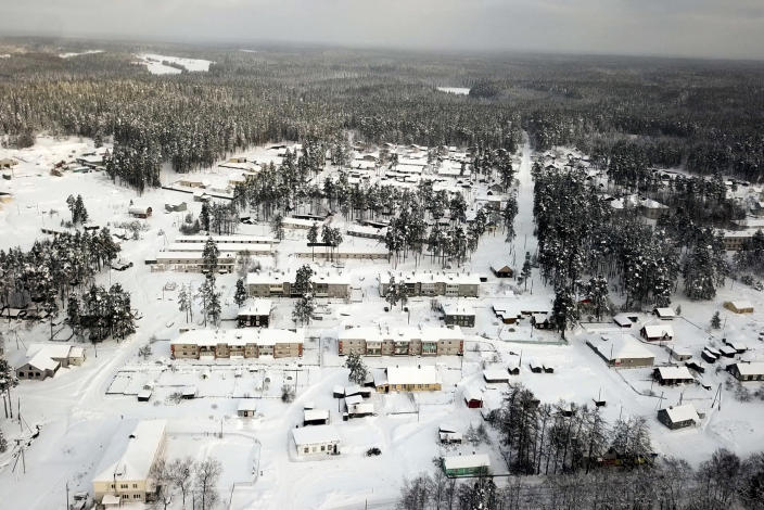 Snow coats the village of Ikhala in Russia's Karelia region, Tuesday, Feb. 16, 2021. The village of wooden houses — carved out of a dense forest of fir trees near the Finnish border and north of St. Petersburg — is one of several in the Karelia region where Russia's slow rollout of its vaccination campaign has arrived at last. (AP Photo/Kirill Zarubin)