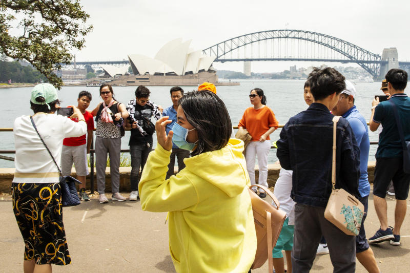 Tourists are seen at Mrs Macquarie's Chair in Sydney wearing face masks.