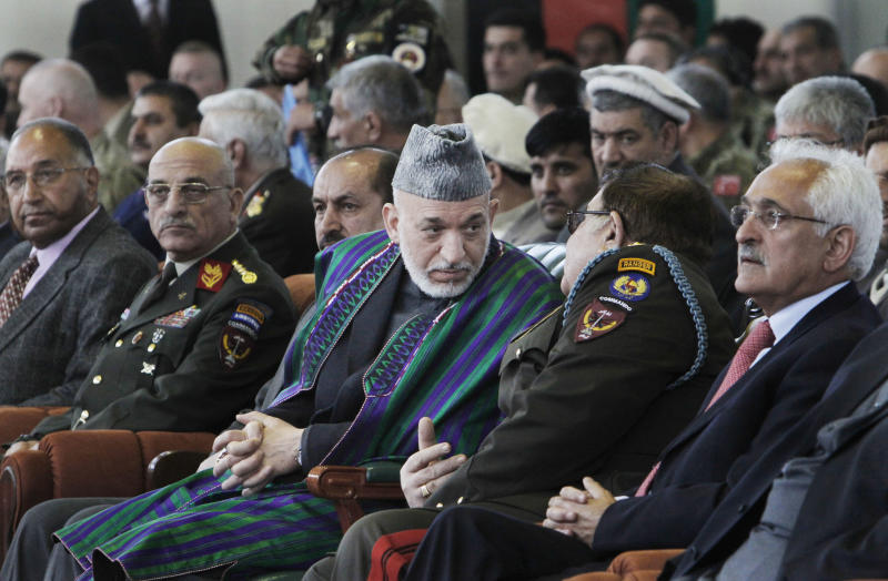"Afghan President Hamid Karzai, center, listens to Defense Minister Abdul Rahim Wardak, unseen, during a graduation ceremony of Afghan military officers in Kabul, Afghanistan, Thursday, March 22, 2012. Afghanistan's president said Thursday that his government is ""taking a magnifying glass"" to proposals for the country's strategic partnership deal with the United States and scrutinizing every detail. (AP Photo/Musadeq Sadeq)"