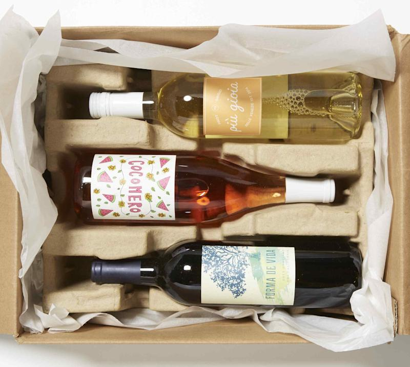 Carboard shipping box filled with a bottle of white wine, rose wine, and red wine