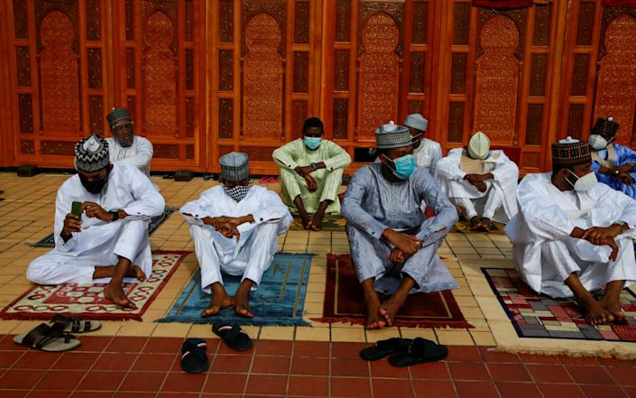 People wearing protective face masks sit on their mats, with some social distance spaces observed between them, during Eid al-Adha prayers at the National Mosque, in Abuja, Nigeria - AFOLABI SOTUNDE/REUTERS