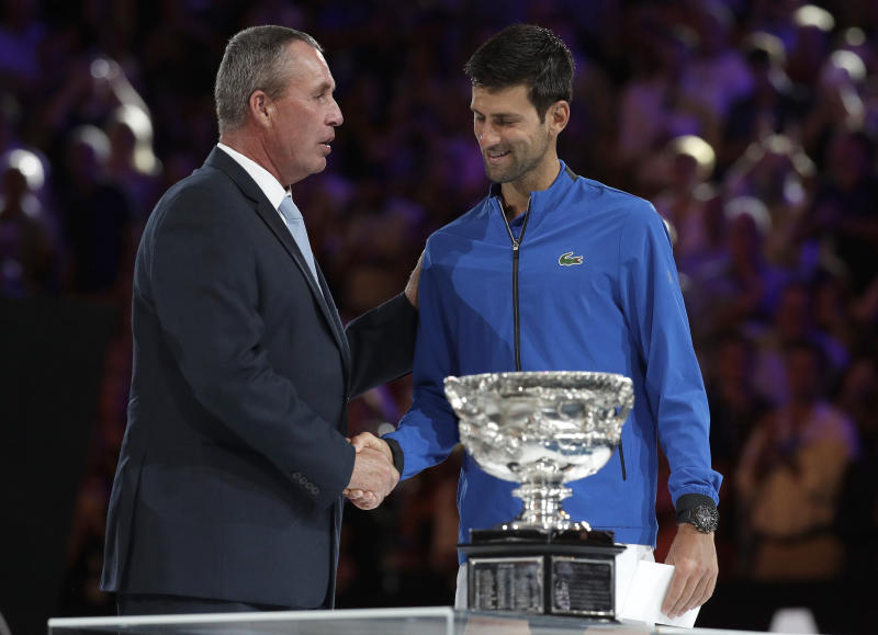 Serbia's Novak Djokovic, right, receives his trophy from Ivan Lendl after defeating Spain's Rafael Nadal in the men's singles final at the Australian Open tennis championships in Melbourne, Australia, Sunday, Jan. 27, 2019. (AP Photo/Kin Cheung)