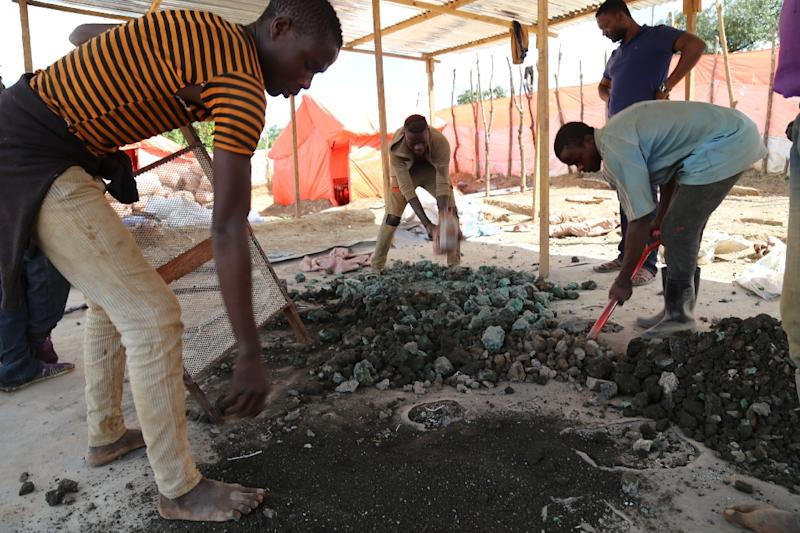 Subsistence miners sort out cobalt and other minerals by a road in southeastern DR Congo (AFP Photo/SAMIR TOUNSI)