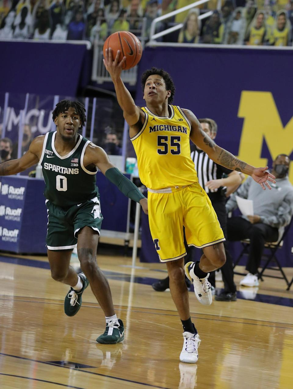 Michigan Wolverines guard Eli Brooks scores against Michigan State Spartans forward Aaron Henry on Thursday, March 4, 2021 at Crisler Center in Ann Arbor.