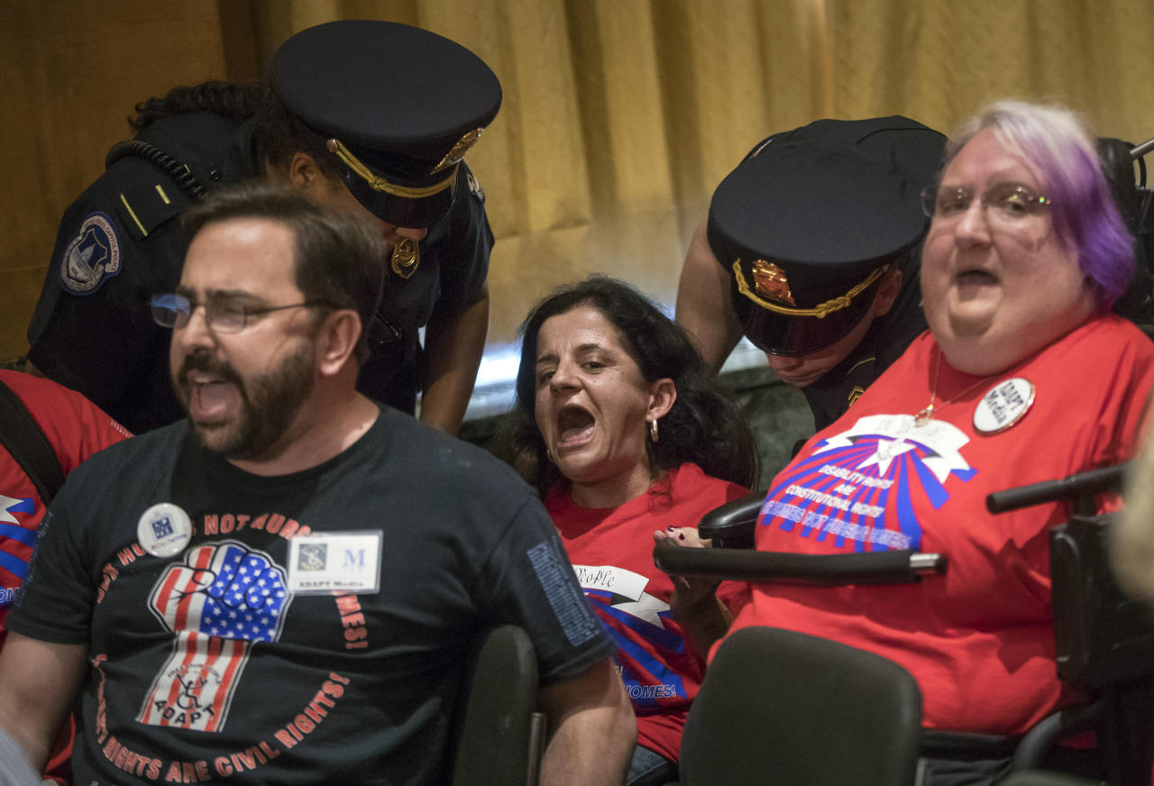 Colleen Flanagan of Boston, and other activists in wheelchairs opposed to the GOP's Graham-Cassidy health care repeal bill, are removed by U.S. Capitol Police after disrupting a Senate Finance Committee hearing on the last-ditch GOP push to overhaul the nation's health care system, on Capitol Hill in Washington, Monday, Sept. 25, 2017. (AP Photo/J. Scott Applewhite)