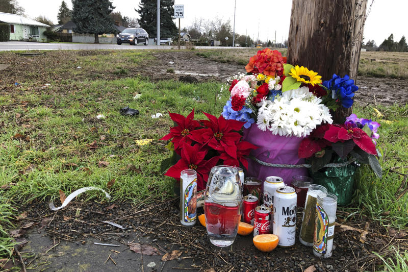 """Flowers, candles, and other objects are shown at a memorial, Thursday, Dec. 12, 2019, at the scene where three Christmas tree farm workers from Guatemala were killed and others were injured in a van crash on Nov. 29, 2019 in Salem, Ore. Immigrant and worker advocates say the crash shed light on """"invisible work"""" by immigrant workers that takes place in Oregon, which has the U.S.'s largest Christmas tree industry. (AP Photo/Andrew Selsky)"""