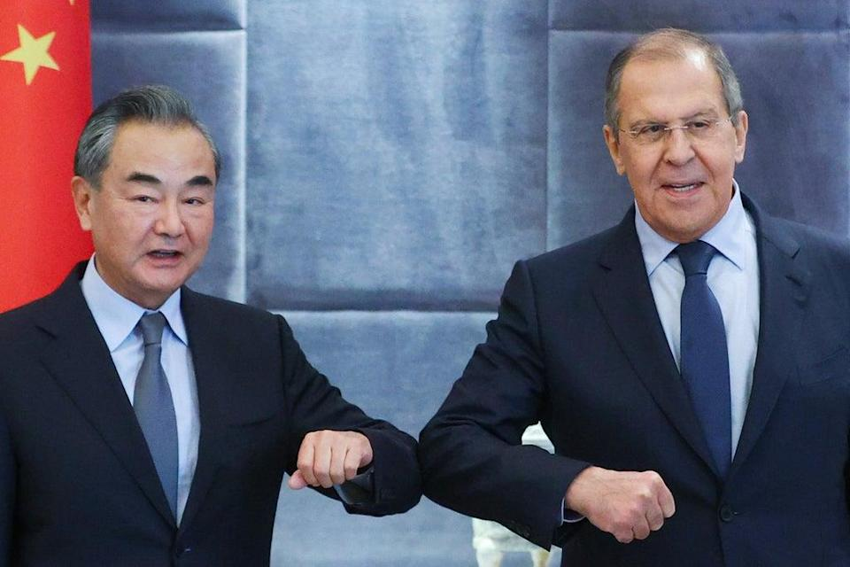 China's Foreign Minister Wang Yi (L) and his Russian counterpart Sergei Lavrov bump elbows as they meet for talks (Russian Foreign Ministry/TASS)