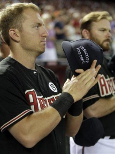 Arizona Diamondbacks shortstop Cliff Pennington , left, acknowledges the Prescott Fire Department and fans before a game between the Colorado Rockies on Friday, July 5, 2013, in Phoenix. Prescott lost 19 fire fighters during a fire in Yarnell. (AP Photo/Rick Scuteri)