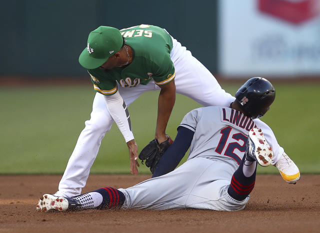 Cleveland Indians' Francisco Lindor (12) is tagged out in an attempted steal of second base, by Oakland Athletics shortstop Marcus Semien during the first inning of a baseball game Friday, June 29, 2018, in Oakland, Calif. (AP Photo/Ben Margot)