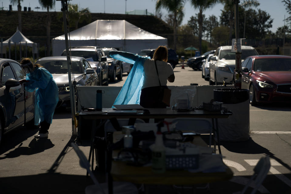 A medical worker puts on a protective gown as cars line up for COVID-19 testing at a testing site set up at the OC Fairgrounds in Costa Mesa, Calif., Monday, Nov. 16, 2020. (AP Photo/Jae C. Hong)