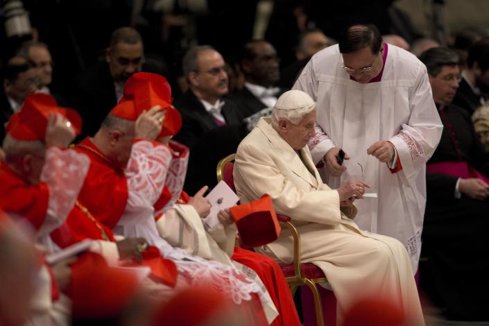 An aide gives glasses to Pope Emeritus Benedict XVI as he attends a consistory inside the St. Peter's Basilica at the Vatican, Saturday, Feb.22, 2014. Benedict XVI has joined Pope Francis in a ceremony creating the cardinals who will elect their successor in an unprecedented blending of papacies past, present and future. (AP Photo/Alessandra Tarantino)