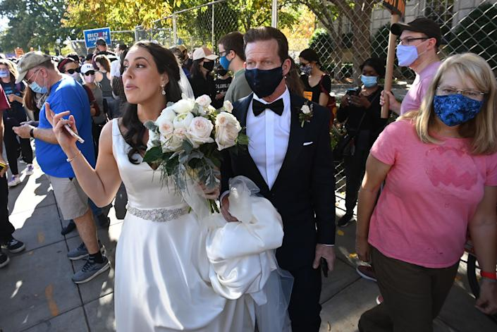 <p>Newlyweds walk through Black Lives Matter Plaza as people celebrate across from the White House</p>AFP via Getty Images