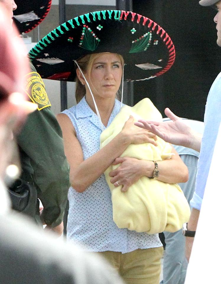 """<p class=""""MsoNormal""""><span style="""""""">If you were looking forward to seeing Jennifer Aniston's upcoming film """"We're the Millers,"""" you're probably even more interested after seeing this wacky shot of a frumpily dressed Aniston on set in New Mexico wearing a giant sombrero, cradling a fake baby, and talking to a border patrol agent. The comedy follows a drug dealer who creates a fake family – including a housewife played by Aniston – to help him move a shipment of marijuana into Mexico. Note to Aniston's character: When trying to keep a low profile, the smaller the hat the better. (9/25/2012) <br></span></p>"""