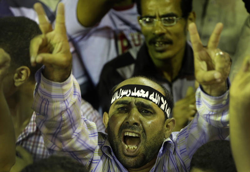 "A supporter of Egypt's ousted President Mohammed Morsi, flashes victory sign as he shouts slogans during a demonstration in front of Cairo University, where protesters have installed their camp in Giza, southwest of Cairo, Egypt, late Wednesday, July 17, 2013. The European Union's top foreign policy official urged Egypt's interim leaders and supporters of the ousted Islamist president Wednesday to cooperate in a political process that moves the country toward democracy. But Morsi's backers expanded their protests in Cairo, denouncing the new government and casting doubt on the prospects for reconciliation. The Arabic headband on his head reads""No God, only the God and Mohammed is God's prophet."" (AP Photo/Hussein Malla)"