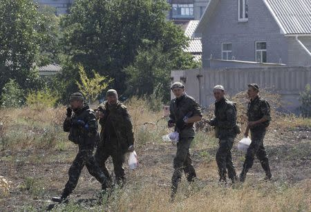 """Soldiers of Ukrainian self-defence battalion """"Azov"""" walk near a checkpoint in the southern coastal town of Mariupol, September 5, 2014. REUTERS/Vasily Fedosenko"""