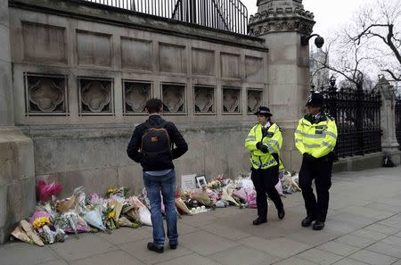 Police officers walk past floral tributes placed near the scene of an attack close to the Houses of Parliament, in London