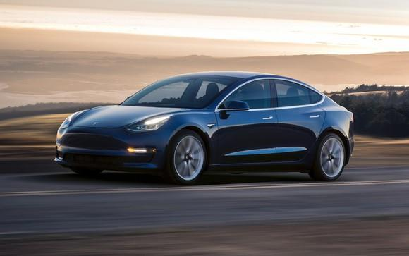 Dark-colored Tesla Model 3 vehicle on a road in front of an open landscape of rolling hills and layered clouds.
