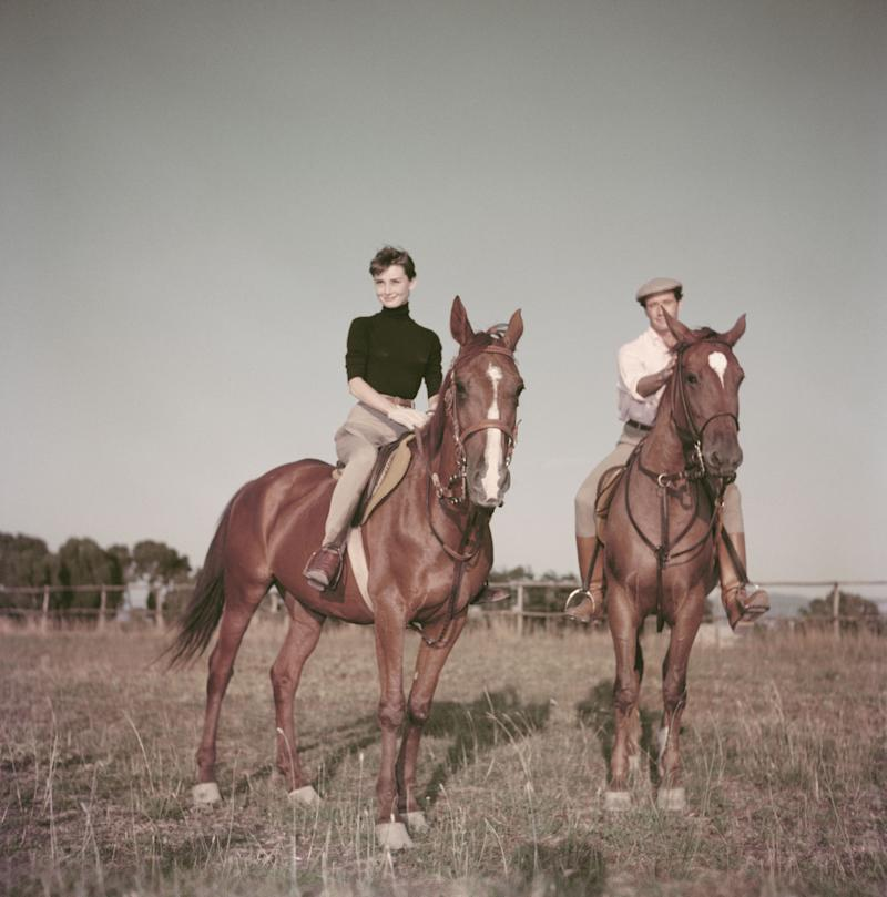 The actress, photographed with her first husband, Mel Ferrer, wears a turtleneck while riding a horse near Rome, 1955.