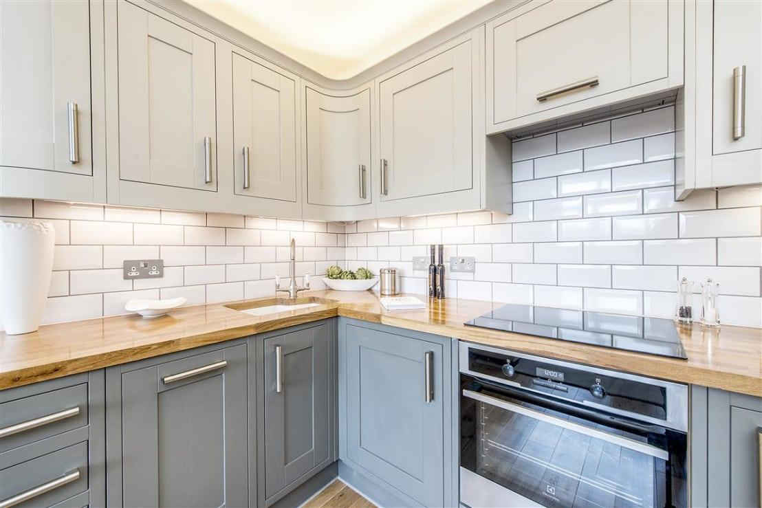 <p>We are just in love with the chic design of this L-shaped kitchen – although it's modern, we can pick up hints of the classic style here and there (especially the shaker cabinetry), resulting in a slightly timeless look.</p><p>Thanks to stainless steel finishes and glossy tilework (that backsplash is so eye-catching!), the incoming natural lighting is bounced around, making this culinary corner light up.</p>  Credits: homify / Maxmar Construction LTD