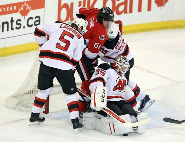 Ottawa Senators' Mark Stone (61) is checked by New Jersey Devils' Adam Larsson (5) and Anton Volchenenkov (29) as Devils goaltender Cory Schneider stops the puck during first-period NHL hockey game action in Ottawa, Ontario, Thursday, April 10, 2014. (AP Photo/The Canadian Press, Fred Chartrand)