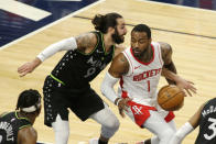 Minnesota Timberwolves guard Ricky Rubio (9) reaches around Houston Rockets guard John Wall (1) in the first quarter during an NBA basketball game, Friday, March 26, 2021, in Minneapolis. (AP Photo/Andy Clayton-King)