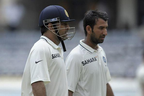 Indian cricket team captain Mahendra Singh Dhoni (L) and Cheteshwar Pujara walk off the pitch during the second day of the first Test cricket match between India and New Zealand at the Rajiv Gandhi International cricket stadium in Hyderabad on August 24, 2012. AFP PHOTO / Noah SEELAM (Photo credit should read NOAH SEELAM/AFP/GettyImages)