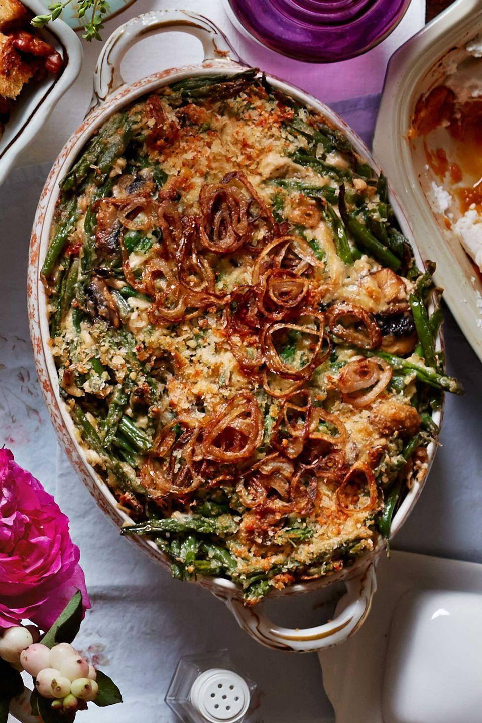 """<p>Skip the store-bought crispy onions. This once-a-year dish deserves to be topped with handmade fried shallots! A rich sauce and a touch of Parmesan elevates this traditional side. </p><p><strong><a href=""""https://www.countryliving.com/food-drinks/recipes/a5868/green-bean-casserole-fried-shallots-recipe-clx1114/"""" rel=""""nofollow noopener"""" target=""""_blank"""" data-ylk=""""slk:Get the recipe"""" class=""""link rapid-noclick-resp"""">Get the recipe</a>.</strong></p>"""