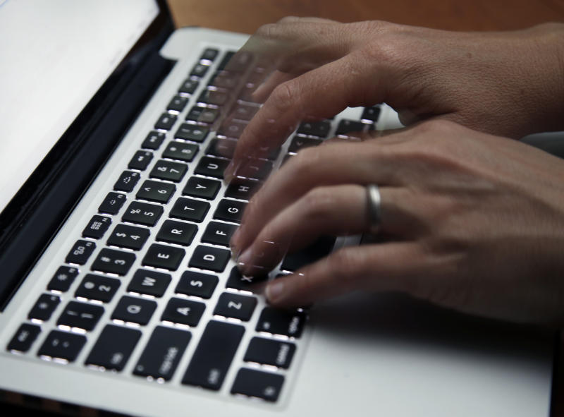 FILE - This June 19, 2017 file photo shows a person working on a laptop in North Andover, Mass. The U.S. internet won't get overloaded by spikes in traffic from the millions of Americans now working from home to discourage the spread of the new coronavirus, experts say. But connections could stumble for many if too many family members try to videoconference at the same time. (AP Photo/Elise Amendola, File)