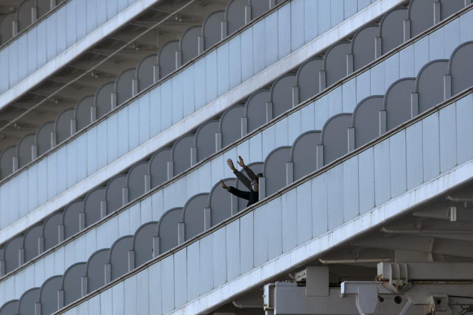 Two people wave from the quarantined Diamond Princess cruise ship in Yokohama, near Tokyo, Tuesday, Feb. 11, 2020. Japan's Health Minister Katsunobu Kato said the government was considering testing everyone remaining on board and crew on the Diamond Princess, which would require them to remain aboard until results were available. (AP Photo/Jae C. Hong)