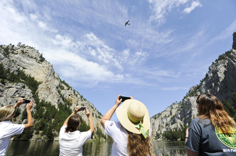 Spectators use cell phones to capture Miss Montana fly over and drop wreaths Monday, Aug. 5, 2019, in the Gates of the Mountains in Montana. The plane dropped twelve wreaths commemorating the twelve smokejumpers who died fighting the Mann Gulch Fire 70 years ago. (Thom Bridge/Independent Record via AP)