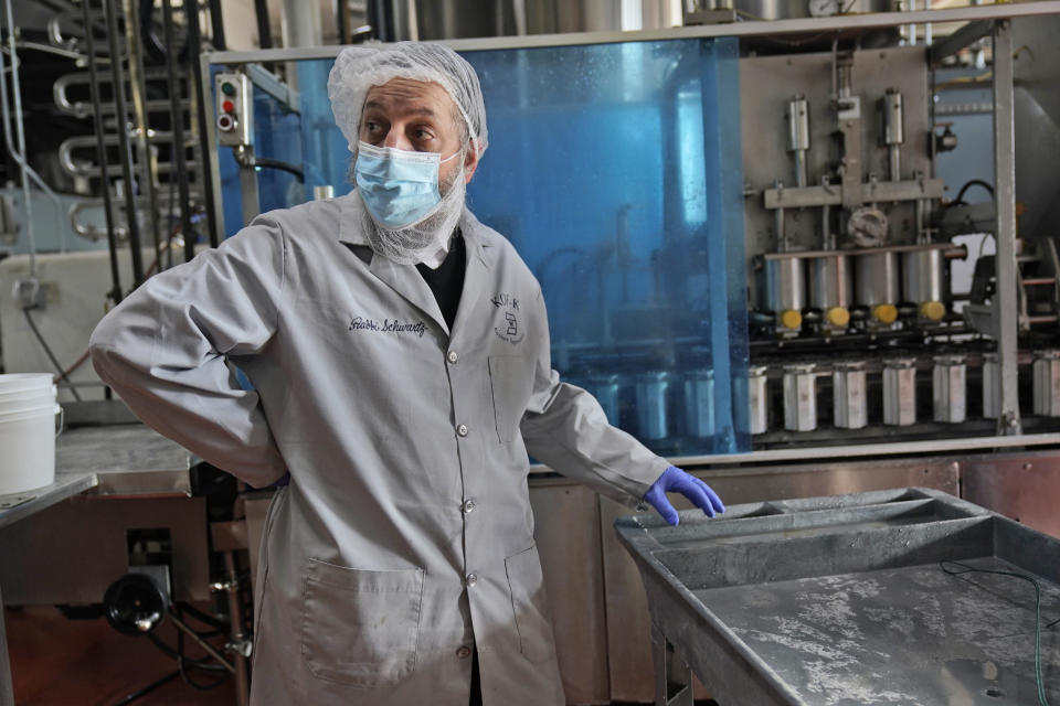 Rabbi Joseph Schwartz supervises the koshering of the production line and instruments used for Hanan Products' kosher-for-passover production run, Thursday, Jan. 7, 2021, in Hicksville, N.Y. (AP Photo/Seth Wenig)
