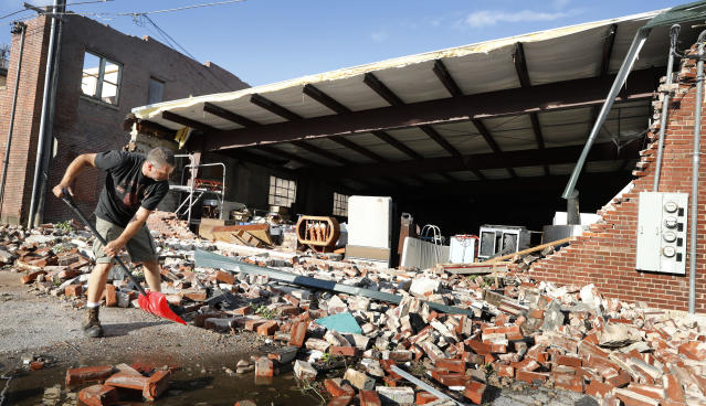 <p>Roy Schweinebart, of Marshalltown, Iowa, shovels bricks from a tornado-damaged building near Main Street, Thursday, July 19, 2018, in Marshalltown, Iowa. Several buildings were damaged by a tornado in the main business district in town including the historic courthouse. (Photo: Charlie Neibergall/AP) </p>