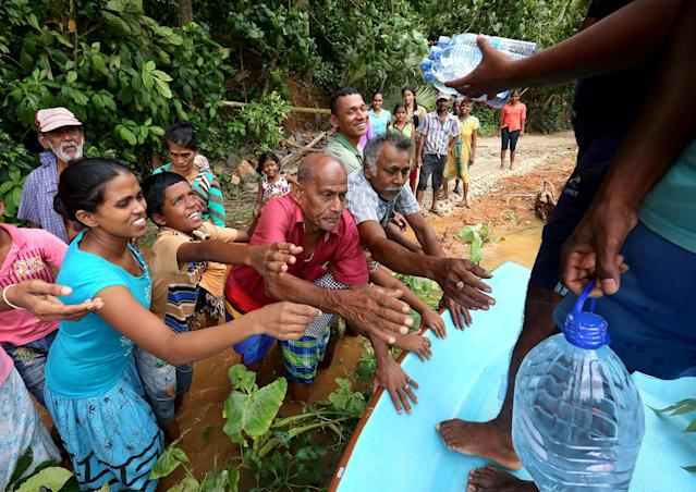 <p>Sri Lankan flood victims receive drinkable water bottles by Sri Lankan Navy soldiers at Godagama, Matara, southern part of Sri Lanka, May 30, 2017. (Tharaka Basnayaka/NurPhoto via Getty Images) </p>