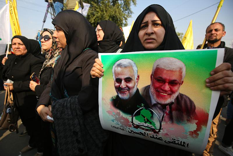 "Women taken part in the funeral procession of Iraqi paramilitary chief Abu Mahdi al-Muhandis (poster-R) , Iranian military commander Qasem Soleimani (poster-L), and eight others in the capital Baghdad's district of al-Jadriya, near the high-security Green Zone, on January 4, 2020. - Thousands of Iraqis chanting ""Death to America"" joined the funeral procession for Iranian military commander Qasem Soleimani and Muhandis, both killed in a US air strike. The cortege set off around Kadhimiya, a Shiite pilgrimage district of Baghdad, before heading to the Green Zone government and diplomatic district where a state funeral was to be held attended by top dignitaries. In all, 10 people -- five Iraqis and five Iranians -- were killed in Friday morning's US strike on their motorcade just outside Baghdad airport. (Photo by AHMAD AL-RUBAYE / AFP) (Photo by AHMAD AL-RUBAYE/AFP via Getty Images)"