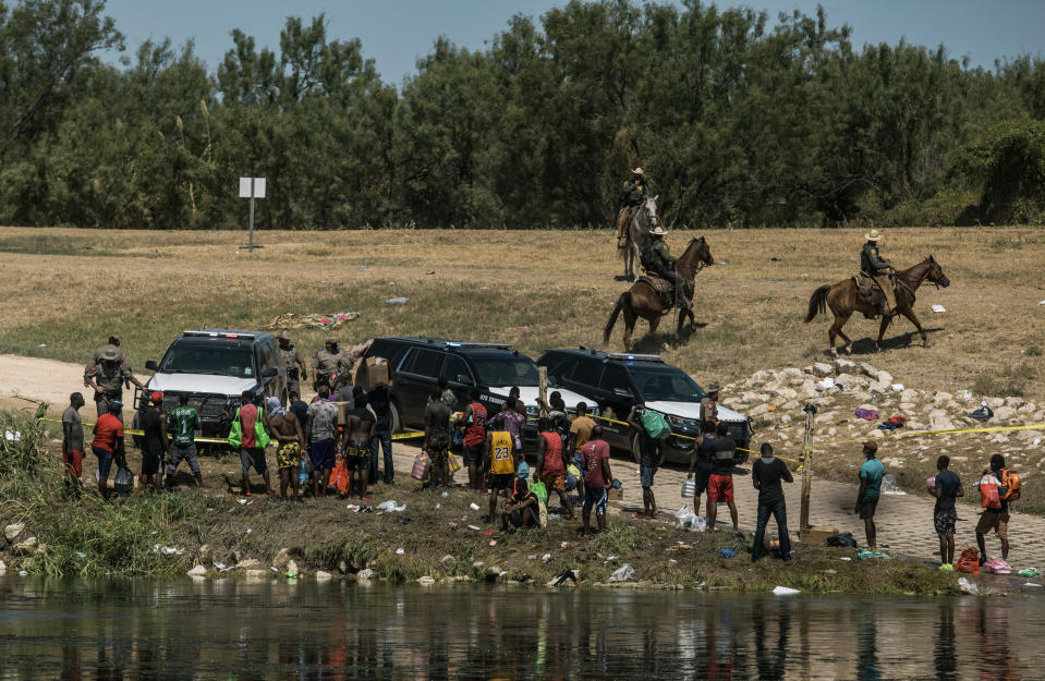 U.S. border patrol officers contain a group of migrants on the shore of the Rio Grande after they crossed from Ciudad Acuña, Mexico, into Del Rio, Texas, Sunday, Sept. 19, 2021. Thousands of Haitian migrants have been arriving to Del Rio, Texas, as authorities attempt to close the border to stop the flow of migrants. (AP Photo/Felix Marquez)