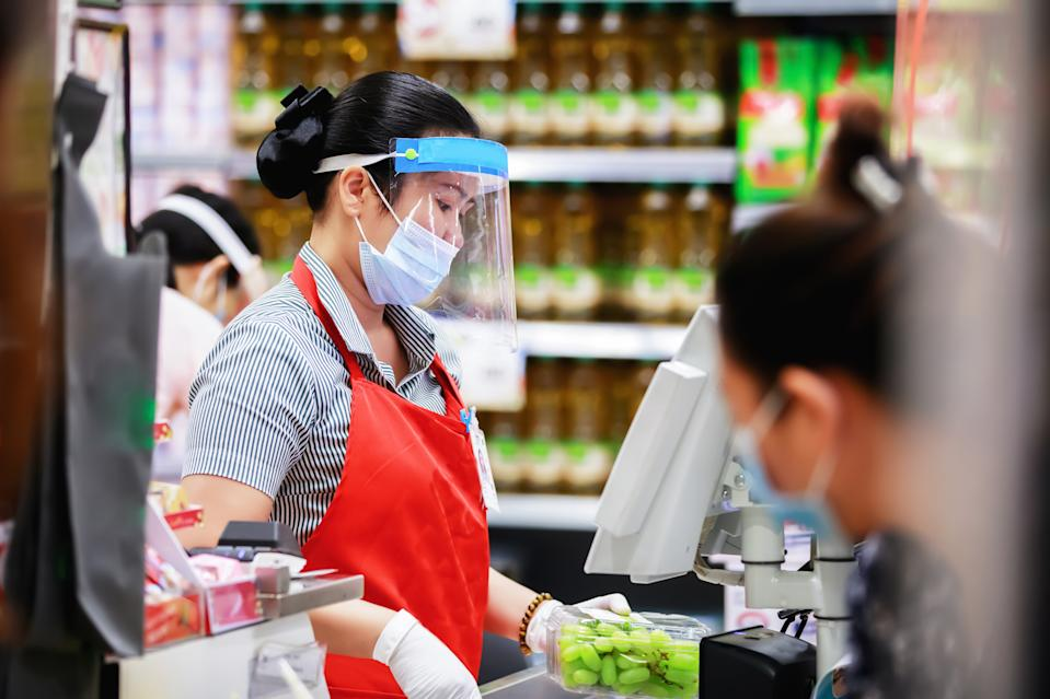 female supermarket cashier in medical protective mask working at supermarket. covid-19 spreading outbreak
