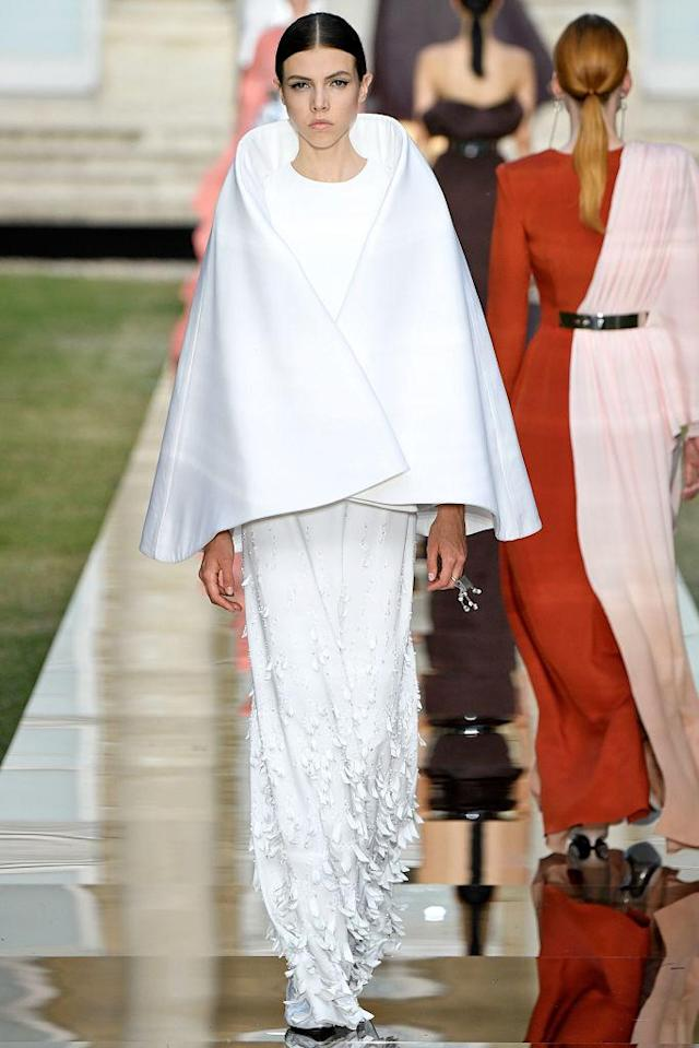 <p>Model wears a simple white cape over a white gown from the Givenchy fall 2018 couture collection. (Photo: Getty Images) </p>