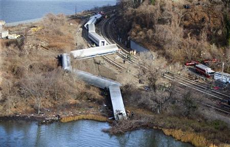 Emergency workers examine the site of a Metro-North train derailment in the Bronx borough of New York December 1, 2013. REUTERS/Carlo Allegri
