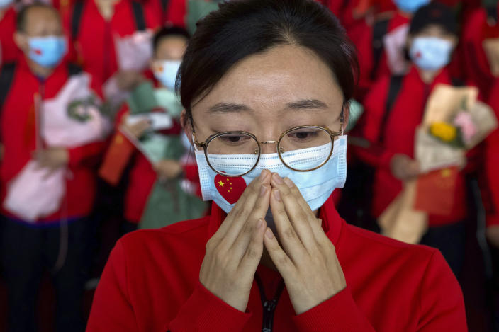 FILE - In this April 8, 2020, file photo, a medical worker from China's Jilin Province reacts as she prepares to return home at Wuhan Tianhe International Airport in Wuhan in central China's Hubei Province. The Chinese city of Wuhan is looking back on a year since it was placed under a 76-day lockdown beginning Jan. 23, 2020. (AP Photo/Ng Han Guan, File)