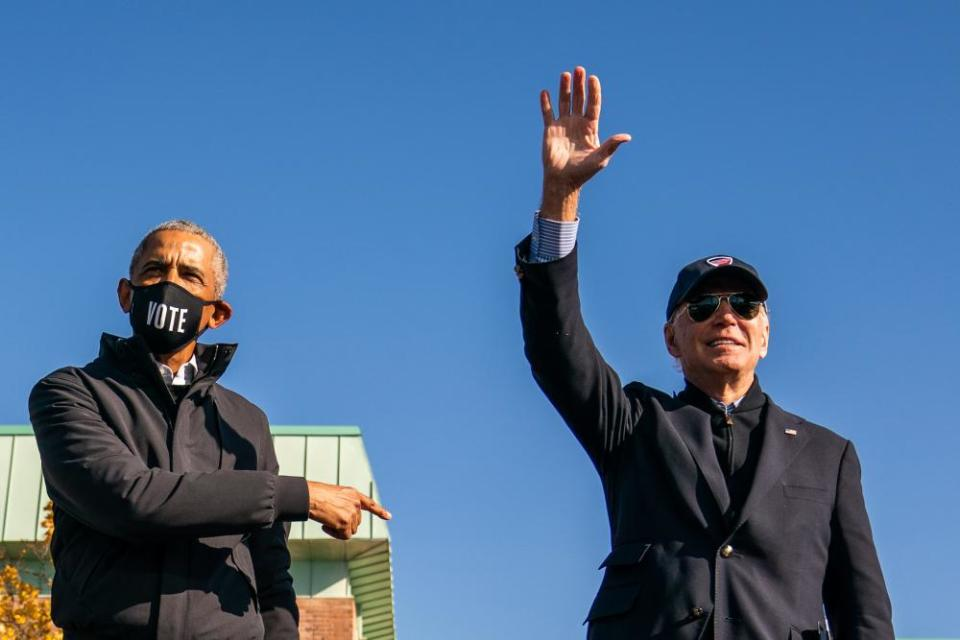 Barack Obama and Joe Biden on stage during a mobilization event at Northwestern high school in Flint, Michigan, on 31 October.