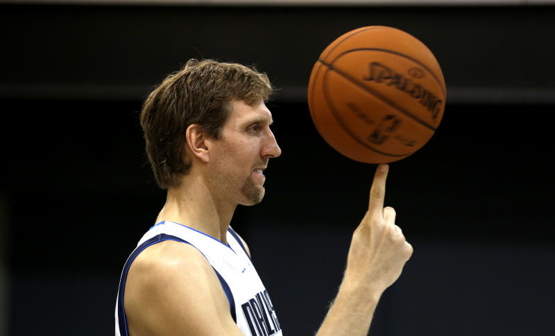 Dallas Mavericks power forward Dirk Nowitzki (41) of Germany spins a ball as poses for a photo during the basketball team's media day Monday, Sept. 30, 2013, in Dallas. (AP Photo/LM Otero)