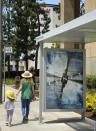 """FILE - In this June 27, 2020, file photo, people walk by a poster promoting the long-awaited Christopher Nolan film """"Tenet,"""" in Los Angeles. The only post-shutdown films to crack the top 10 in 2020 are Nolan's """"Tenet,"""" in eighth place with $57.2 million and the animated family sequel """"The Croods: A New Age,"""" which was released at Thanksgiving and has earned $30.8 million so far to put it in 10th place. (AP Photo/Anthony McCartney, File)"""