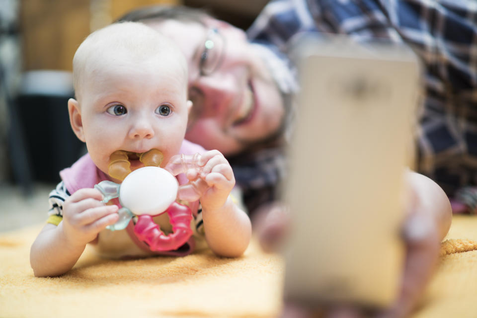 Young father with his baby daughter lying together on the floor and make selfie and have some video-conversation via the cellphone. Minsk, Belarus, Eastern Europe.