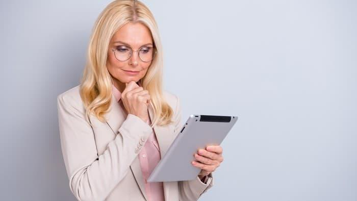 Portrait of a blonde woman holding a tablet