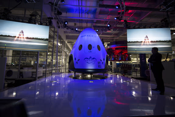 SpaceX CEO Elon Musk stands near the company's Dragon V2 manned space capsule during its public unveiling on May 29, 2014. The seven-person Dragon V2 space capsule is SpaceX's entry to fly NASA astronauts to the International Space Station.